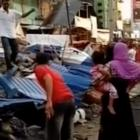 People stand next to the rubble of collapsed buildings following an earthquake in Pidie Jaya,...