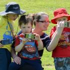 Playing an augmented reality smartphone game at Caversham Reserve yesterday are Eloise Sime and...