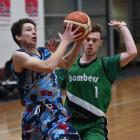 Magic guard Benoit Hayman drives to the basket while trying to stop him is Bombers' guard AJ Auld...