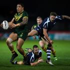 Tyson Frizell of Australia powers past Ben Hellewell and Euan Aitken of Scotland during the Four...