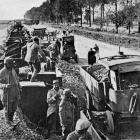 A train load of flints for road maintenance near the front in France is unloaded on to trucks. -...