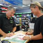 Paper Plus Wanaka manager Chris Lumsden takes an order from Penny Riley in Wanaka yesterday for a...