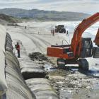 Contractors remove rocks and debris washed up on St Clair Beach during recent severe weather, and...