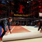 Workers lay the red carpet in front of the 'Berlinale Palace' cinema for the upcoming 67th Berlin...