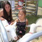 Jessica and daughter Jahleigha (2) Nichol, both of Alexandra, play with goats at the Central...