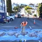 Artist Jenny McCracken works on the new 3-D pedestrian crossing with Downer contractor Nathan...