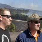 Simon Grace (L) and Hamish Tovey look towards Mr Grace's family home stood in the Port Hills...