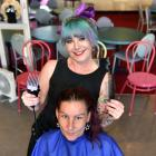 Hairdresser Stacey Warrington cuts Ange Whelan's hair at Heff's Lounge Bar, as part of her...