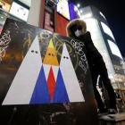Japanese graffiti artist 281 Antinuke poses for a photo with his sticker art depicting US...