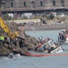 Members of the salvage team and Otago Regional Council staff at work on Holmes Wharf during the...