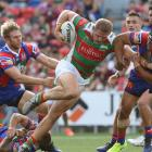 George Burgess of the Rabbitohs is tackled by the Knights defence during the round three match....