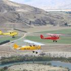 Three Tiger Moths fly in formation over the Clutha River south of Luggate, towards Bendigo and on...