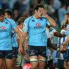 Waratahs captain David Dennis looks dejected after losing the round five Super Rugby match...