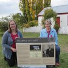 Central Otago District Council property facilities manager Christina Martin (left) and Vallance Cottage working group chairwoman Clair Higginson hold an information panel that will be installed near Vallance Cottage in Alexandra. Photo: Pam Jones.