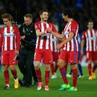 Antoine Griezmann of Atletico Madrid walks alongside Saul Niguez and Stefan Savic after clinching...
