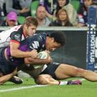 Felise Kaufisi scores for the Melbourne Storm as Blake Ayshford, of the Warriors, tries to stop...