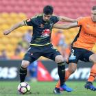 Guilherme Finkler of the Phoenix is pressured by the defence of Luke DeVere of the Roar. Photo:...