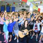 Cathy Irons (centre) leads a group of Hawea Flat School year 3 and 4 pupils through a song...