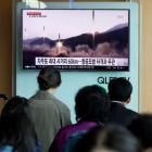 People at a railway station in Seoul watch a TV broadcasting of a news report of an earlier North...