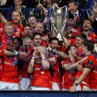 Saracens players celebrate with the trophy after winning the European Rugby Champions Cup. Photo...