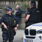 Armed police patrol Manchester's Albert Square as members of the public lay floral tributes and...
