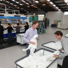 Rick (left) and Steve Wellington prepare sheets to go through a folding machine. Photo: Gregor...