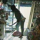 A masked man, armed with a rifle, is captured by a security camera entering the On the Spot Halfway Bush Convenience Store yesterday. The man fled with cash and tobacco. Photo supplied.