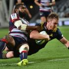 Highlander Gareth Evans goes over to score while tackled by Rebel Marika Koroibete at the Forsyth...