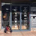 People sit on the footpath outside the Base Streetwear clothing store in Wanaka to use Spark's...