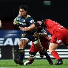 All Black and Highlanders player Malakai Fekitoa (centre) tries to evade a tackle during a Super...