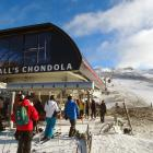 Skiers and snowboarders queue at the base of the new McDougall's Chondola ski lift on opening day...