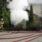 Firefighters attend a house fire at Dublin Bay near Wanaka. Photo: Kerrie Waterworth