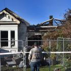 A member of the public surveys the burnt wreckage of a North Rd residence. PHOTO : PETER MCINTOSH...