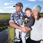 Henley dairy farmers Reon Hamilton and his fiance Emma Keene with son Cooper (2) at a flood...