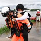 Local resident is rescued by a firefighter after heavy rain hit the area in Asakura. Photo: Reuters