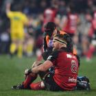 Kieran Read gets his knee looked at after picking up an injury during yesterday's game between...