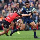 Highlanders centre Malakai Fekitoa tries to fend off Crusaders winger George Bridge last time the...