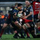 Malakai Fekitoa is tackled in the wet conditions the Highlanders and Crusaders played in on...