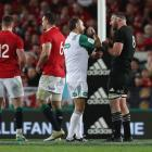 Romain Poite the referee, talks to All Black captain, Kieran Read after he reverses a decision...