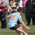 Southern No8 Mika Mafi tries to evade the tackle of University winger Gavin Stark during a...