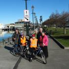 VICTA Dunedin founder Dr Lynley Hood (right) visits the harbourside with (from left) keen walker...