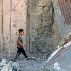 A girl walks on debris in a rebel-held part of the southern city of Deraa, Syria. Photo: Reuters