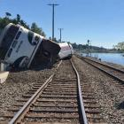A derailed Amtrak passenger train lies on its side before the Chambers Bay Bridge in Washington...