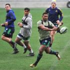 Highlanders winger Waisake Naholo moves the ball while  Malakai Fekitoa (left) and James Lentjes...