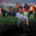 Crusaders coach Scott Robertson breakdances in front of the trophy after his team's victory....