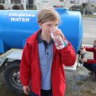 Omakau School pupil Casey Armstrong (8) sips some fresh water as the town closes in on a month...