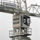 A crane driver climbs to his lofty workplace with its new name displayed on the back of the cab....