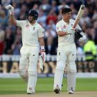 Joe Root (left) and Alistair Cook celebrate Cook's century on the first day of the day-night test...