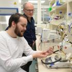 Dr Kiel Hards (foreground), watched by Prof Greg Cook, uses a chemostat in a laboratory at the...