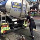 A hospitality worker gets water from a water tanker in the Octagon. Photo: Chris Morris
